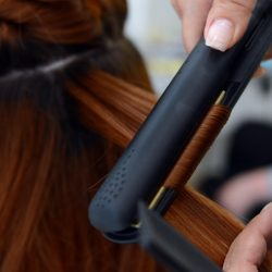 Hairdresser Arzu uses a hair straightener as she dresses a client's hair on August 8, 2012 at the Dry Bar in Berlin. The shop offers to make different blow-dried hairstyles, according to a new trend coming from the US.      AFP PHOTO / BRITTA PEDERSEN    GERMANY OUT        (Photo credit should read BRITTA PEDERSEN/AFP/GettyImages)